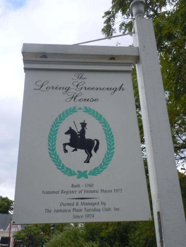 "Picture of a sign hanging on a white post to its right, with trees and sky in the background. The sign says in black script ""The Loring-Greenough House."" Below that is a silhouette of a man with a sword on a rearing-up horse, all framed by painted mint-green ivy. In small print below that, it reads: ""Built -- 1760"" ""National Register of Historic Places 1972"" ""Owned and Managed by"" ""The Jamaica Plain Tuesday Club, Inc."" ""Since 1924"""