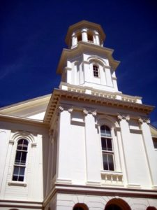 Picture of the front of the Provincetown Library, starting at the tops of the archways and reaching just above the spire. Blue sky background.