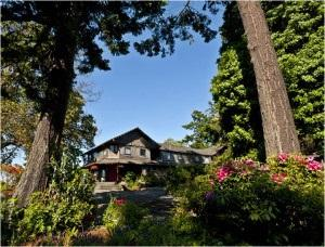 Photo of the Captain Whidbey Inn under a blue sky, surrounded by trees and a pink-flowering bush.